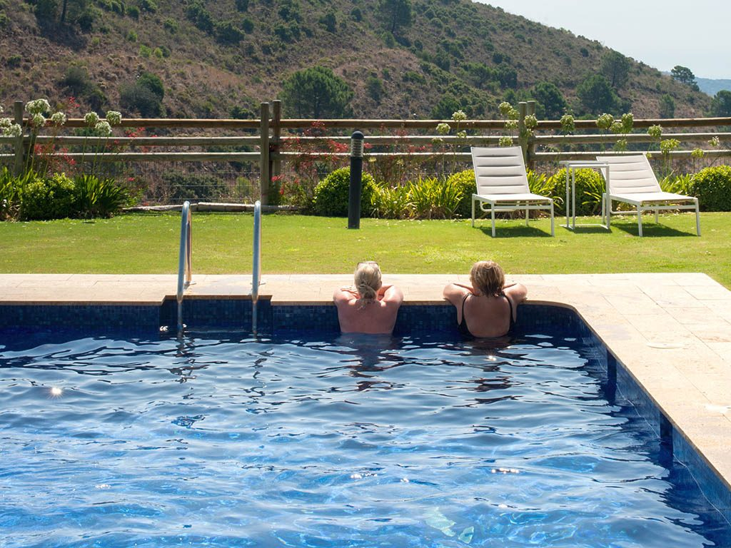 Club members enjoying the outdoor pool with views over Benahavis and the Mediterranean