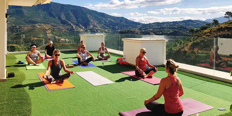 Outdoor yoga class with views over Benahavis mountain range
